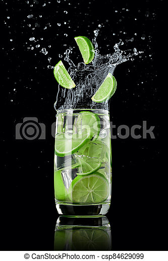 A glass of lime lemonade with ice, splashing in different directions and three slices of lime falling into the glass, on a black background - csp84629099