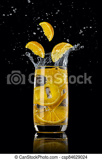 A glass of orange lemonade with ice, splashing in different directions and three orange slices falling into the glass, on a black background - csp84629024