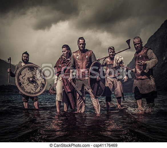 A group of armed Vikings standing on river shore - csp41176469