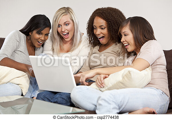 A group of four interracial beautiful young women having fun looking at something surprising and funny on their laptop computer and laughing - csp2774438