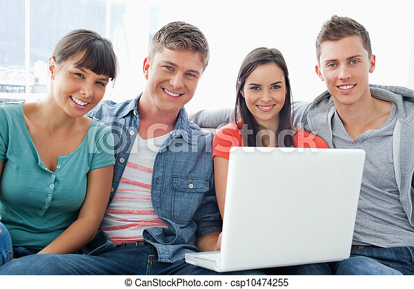 A group of friends sit on the couch together as they hold a laptop and look a the camera  - csp10474255