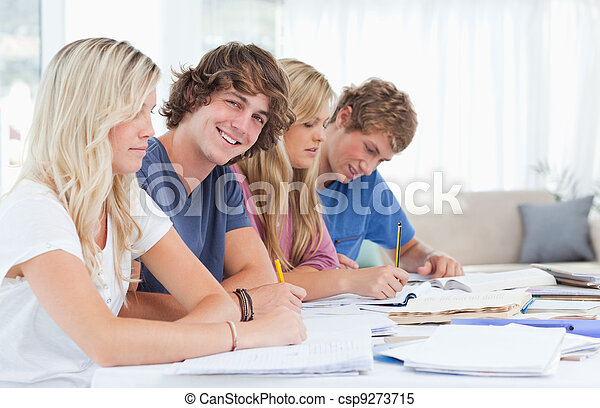 A group of students sitting together as they study hard with one man looking at the camera and smiling  - csp9273715