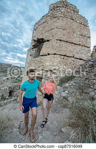 A guy and his girlfriend climb a narrow path to the top of the mountain, in the background is visible - csp87016049