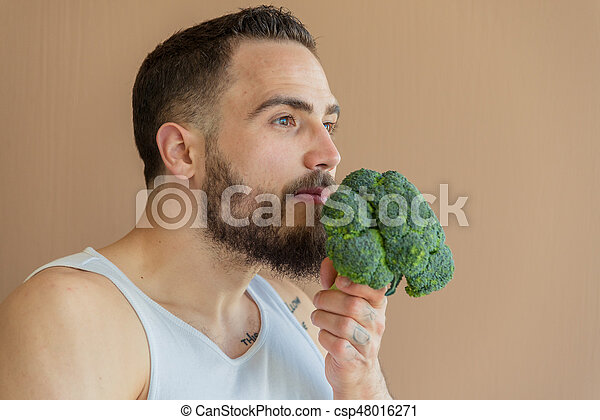 A guy with a beard sniffs broccoli - csp48016271