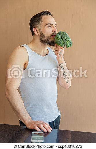 A guy with a beard sniffs broccoli - csp48016273