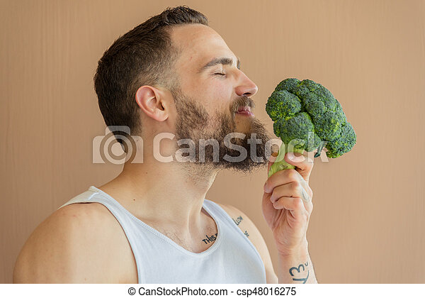 A guy with a beard sniffs broccoli - csp48016275