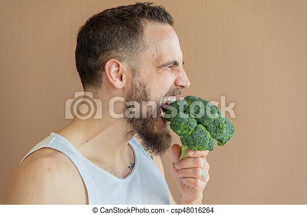A guy with a beard sniffs broccoli - csp48016264
