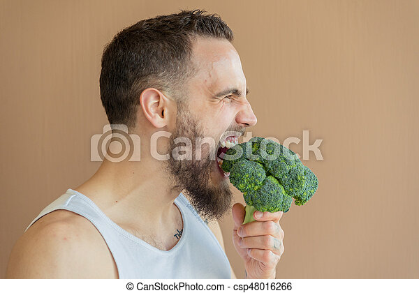 A guy with a beard sniffs broccoli - csp48016266