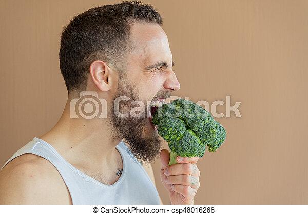 A guy with a beard sniffs broccoli - csp48016268