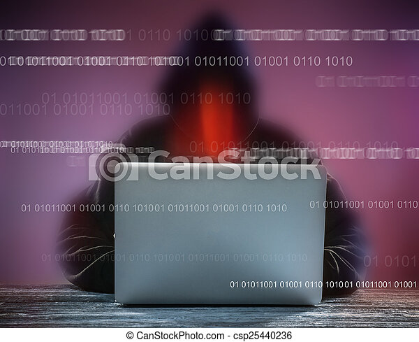 A hacker with a hood with laptop - csp25440236