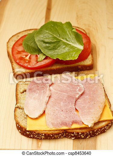 A ham and cheese sandwich with lettuce and cheese on a wood cutting board - csp8453640