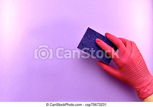 A hand in a rubber glove, a gesture of erasing, removing something from a light purple surface, a washing sponge. - csp75673231