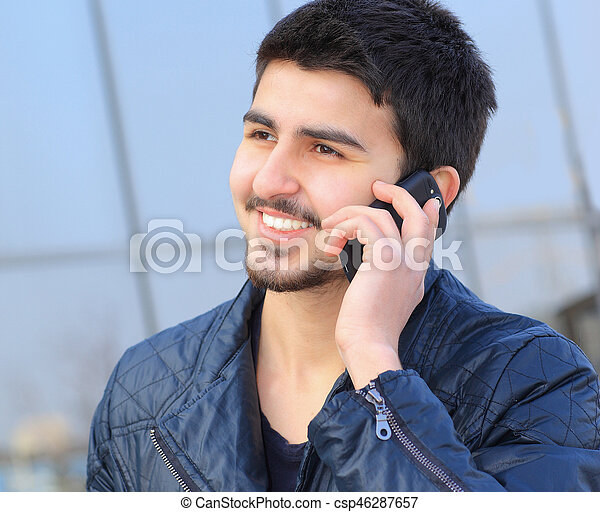 A handsome young man in plain clothes, talking the phone. - csp46287657