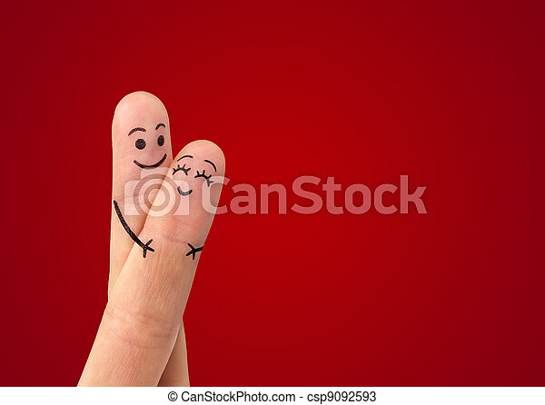 A happy couple in love with painted smiley and hugging - csp9092593