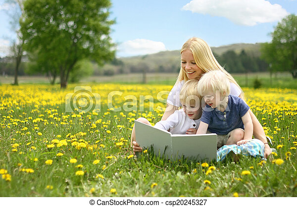 A happy young mother is sitting outside in a meadow of yallow Dandelion flowers, reading a story book to her cute children on a lovely Spring day. - csp20245327