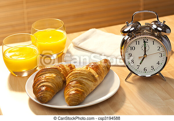 A healthy continental breakfast of croissant pastries, orange juice, oranges Illuminated with golden early morning sunshine and accompanied by a classic alarm clock set at 7am - csp3194588