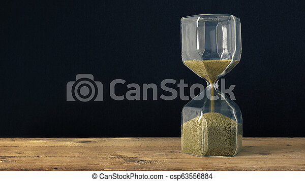 a hourglass on a wooden underground with black background - csp63556884