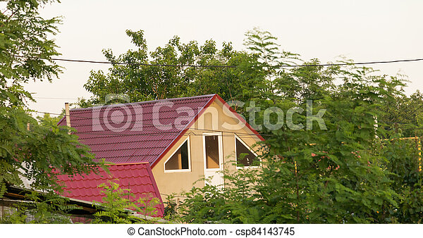A house in the village, surrounded by trees - csp84143745