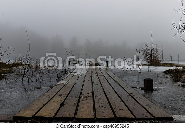 A jetty and a frozen lake in the mist - csp46955245