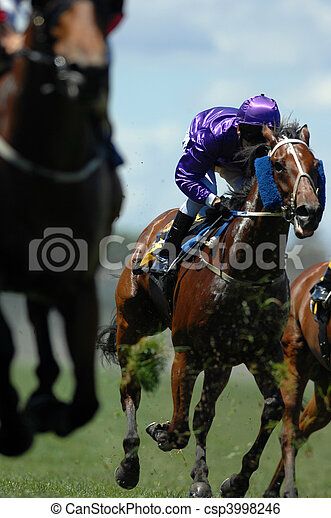 A jockey in action during on a horse during a race. - csp3998246