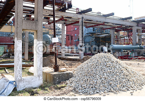 A large pile of rubble, stones on the construction site for the  construction of an oil refinery at an oil refinery, a petrochemical plant