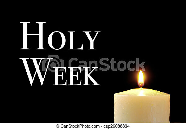 a lit candle and the text holy week - csp26088834