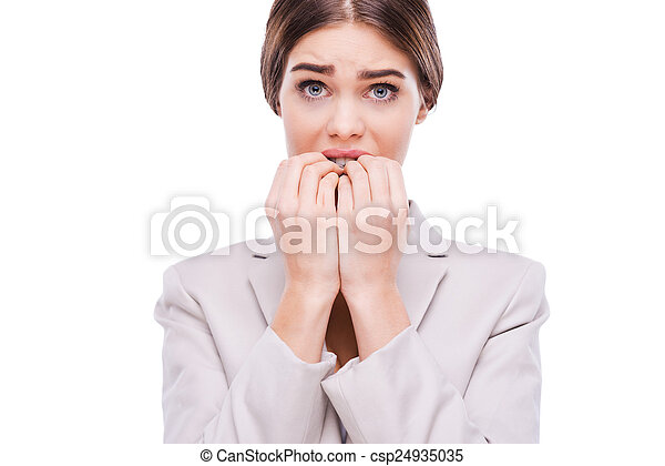 A little bit nervous about this business. Nervous young businesswoman biting her nails while standing against white background - csp24935035