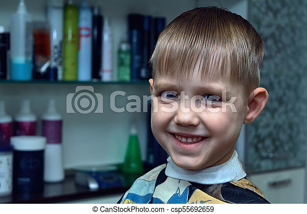 A little boy cut in a hairdresser. He looks at us and smiles. - csp55692659