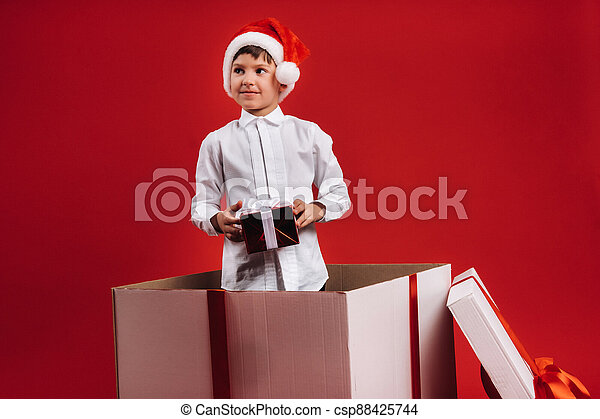 A little boy stands in a gift box with a Christmas present in his hands - csp88425744