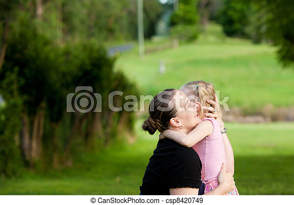 A little girl hugs and embraces her mother outdoors - csp8420749