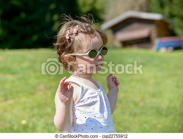 f6b0957fe211 a little girl in the garden with sunglasses - csp22755912