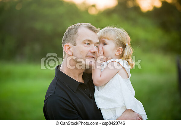 A little girl whispering a secret to her daddy - csp8420746