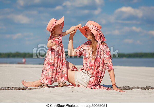 A little girl with her mother in matching sundresses plays in the sand on the beach. Stylish family look - csp89065051