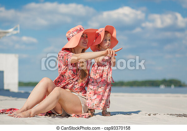A little girl with her mother in matching sundresses plays in the sand on the beach. Stylish family look - csp93370158