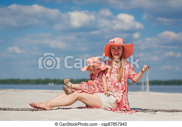 A little girl with her mother in matching sundresses plays in the sand on the beach. Stylish family look - csp87857943