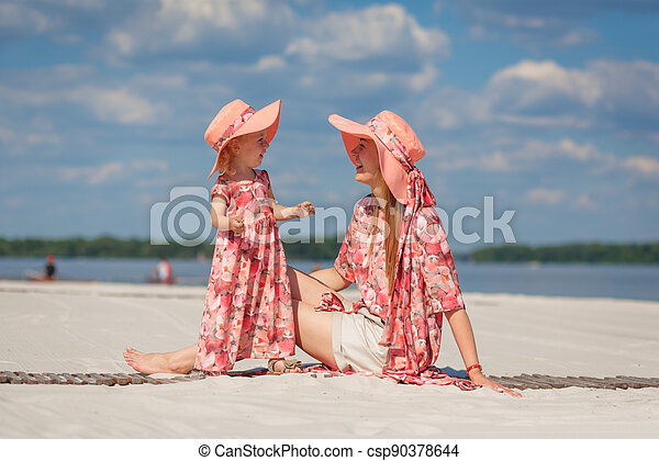 A little girl with her mother in matching sundresses plays in the sand on the beach. Stylish family look - csp90378644