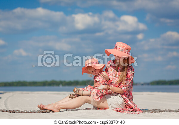 A little girl with her mother in matching sundresses plays in the sand on the beach. Stylish family look - csp93370140