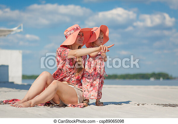 A little girl with her mother in matching sundresses plays in the sand on the beach. Stylish family look - csp89065098