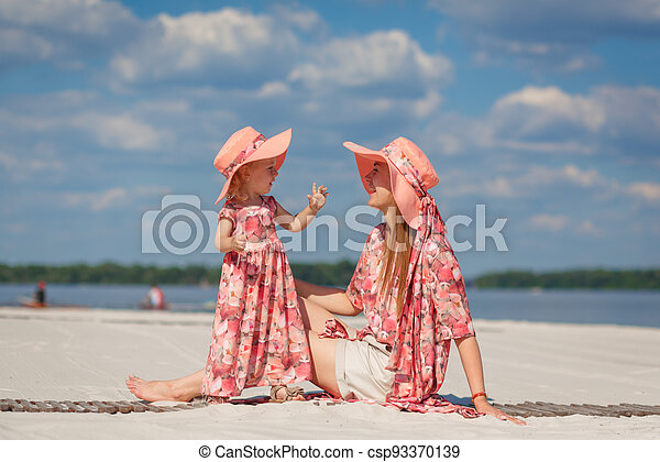 A little girl with her mother in matching sundresses plays in the sand on the beach. Stylish family look - csp93370139