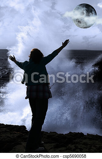 a lone woman raising her arms in awe at the powerful wave and full moon on the cliffs edge in county clare ireland - csp5690058