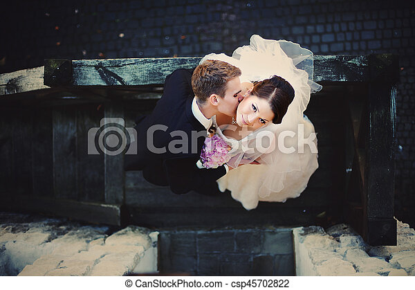 A look from above on the groom kissing bride's neck while they stand on the wooden staira outside - csp45702822
