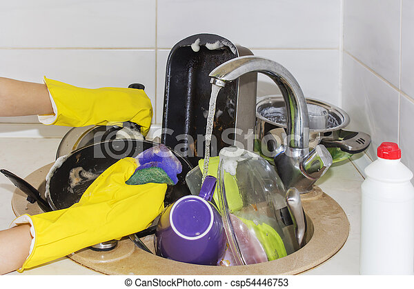A lot of dirty dishes in a sink waiting to be washed. - csp54446753