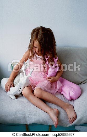 A lovely little girl 4 years old in a pink dress plays with pink deer.The atmosphere of childhood - csp52988597
