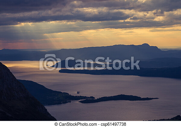 A magnificent sunset scenery over the fjords in Norway in purple tones. Beautiful evening landscape with dramatic sky. - csp61497738