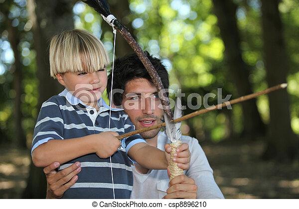 a man and a little boy doing archery in the forest - csp8896210