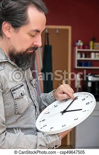 a man changes the time on a clock - csp49647505