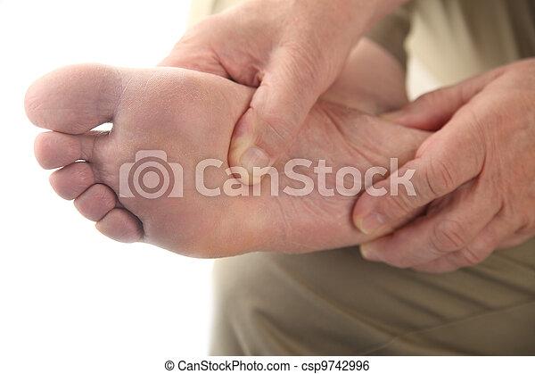 a man checks his aching foot - csp9742996