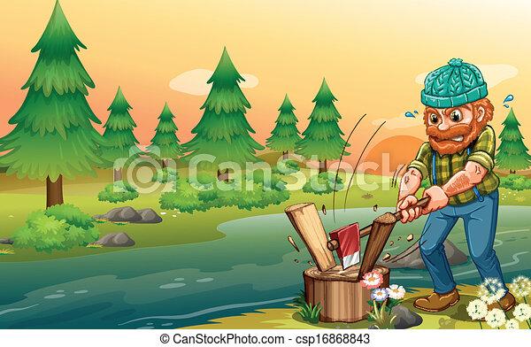 A man chopping woods at the riverbank - csp16868843