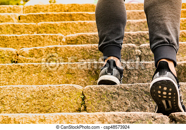 A man climbing the stone steps to success - csp48573924