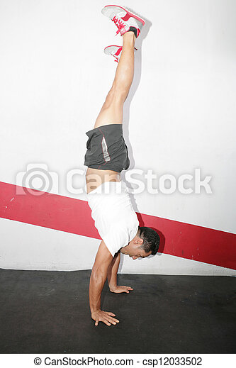 A man does a gymnastic handstand in the gym - csp12033502